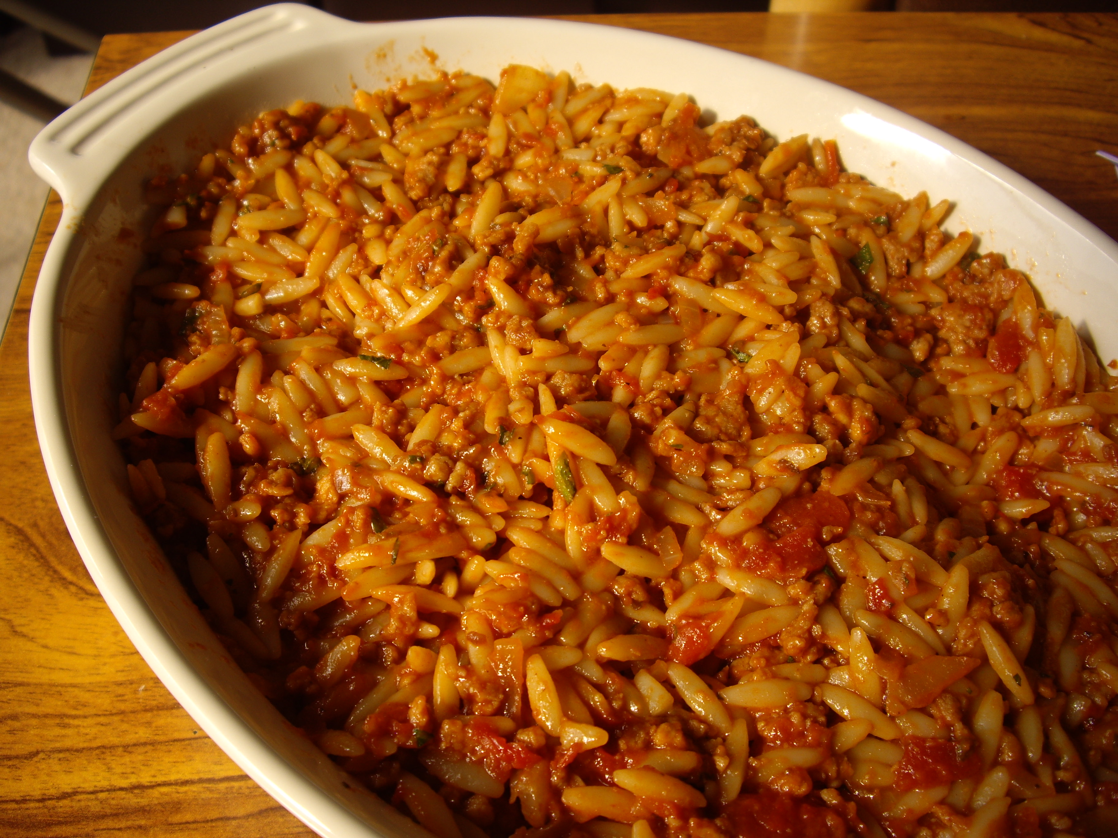 The orzo, tomatoes and beef before being topped with a cheese sauce.